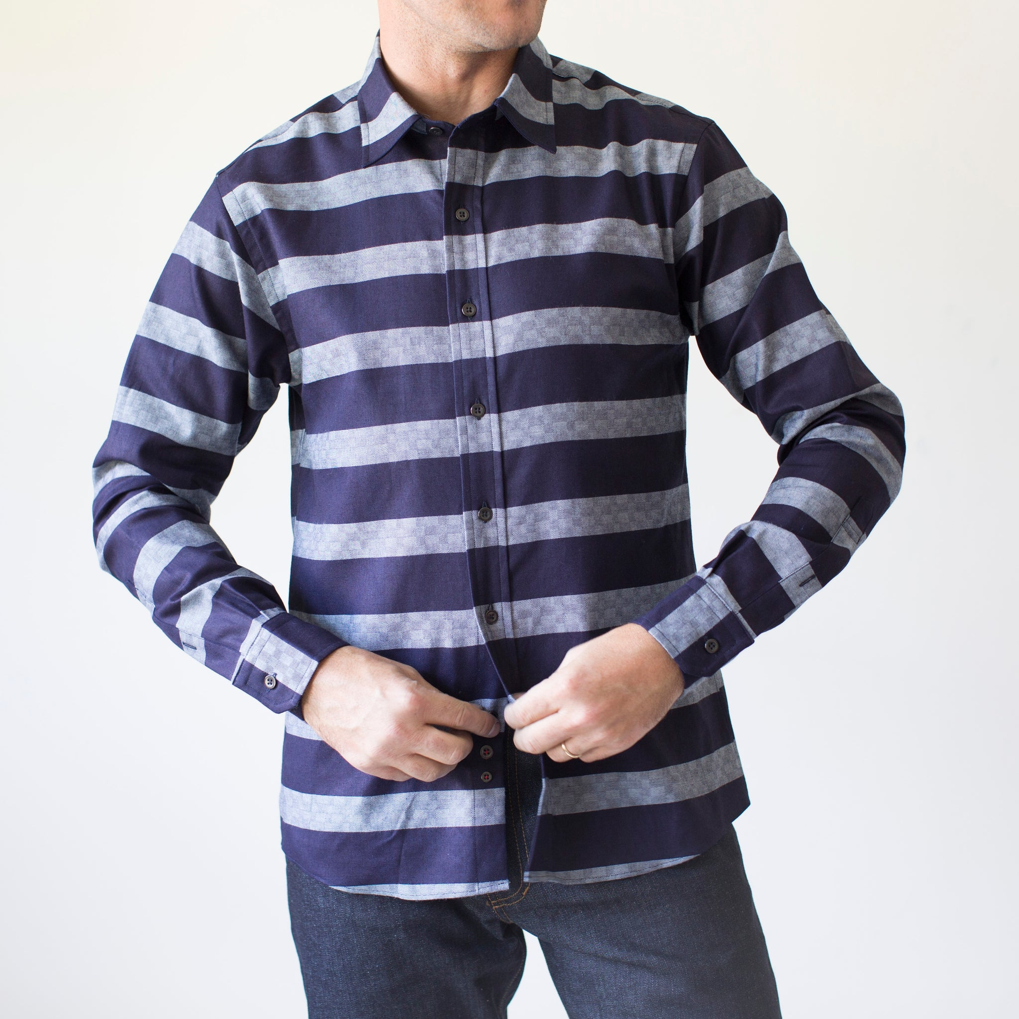 angle: bold indigo stripe  A model wears Raleigh Denim Workshop Classic Button-up men's shirt in indigo and gray stripes, front