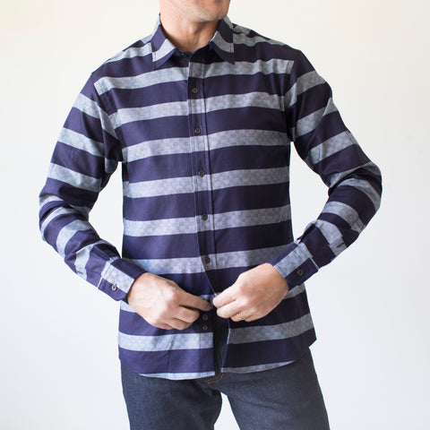 angle: bold indigo stripe | A model wears Raleigh Denim Workshop Classic Button-up men's shirt in indigo and gray stripes, front