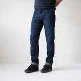 angle hover: jasper  A model wears Raleigh Denim Workshop Alexander work fit men's jeans in dark jasper wash, front view