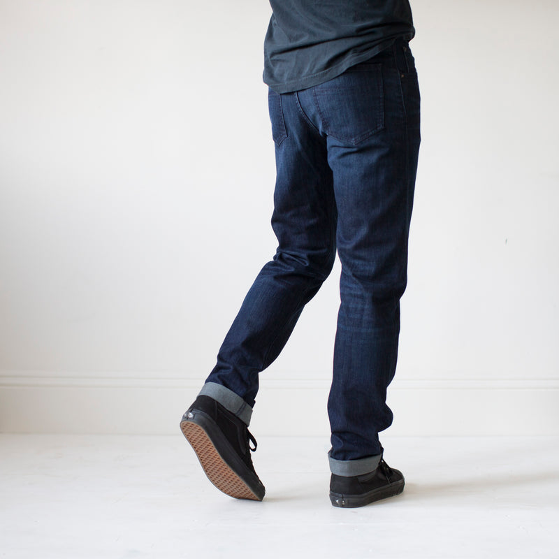 angle: jasper  A model wears Raleigh Denim Workshop Alexander work fit men's jeans in dark jasper wash, back view
