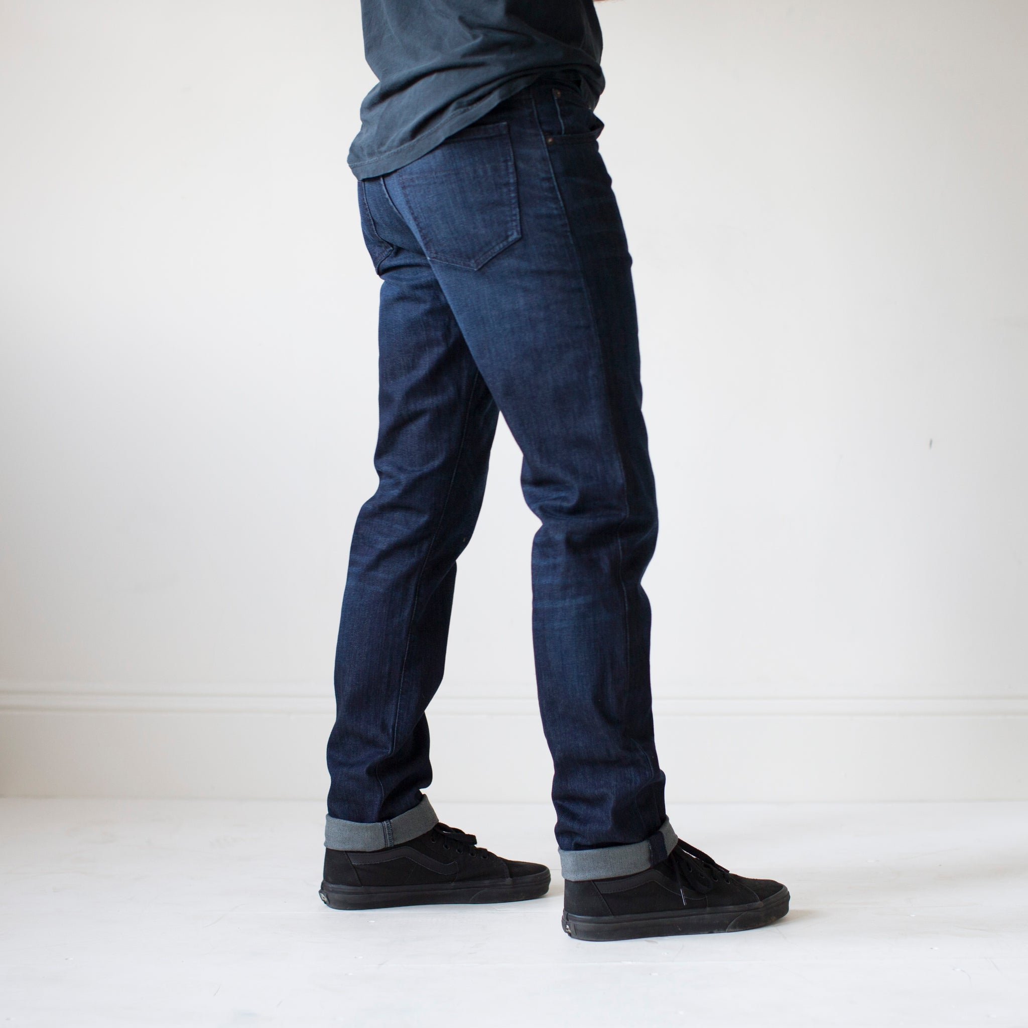 angle: jasper  A model wears Raleigh Denim Workshop Alexander work fit men's jeans in dark jasper wash, side view