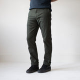 angle: military green  A model wears Raleigh Denim Workshop Jones thin fit pants in dark green, front view