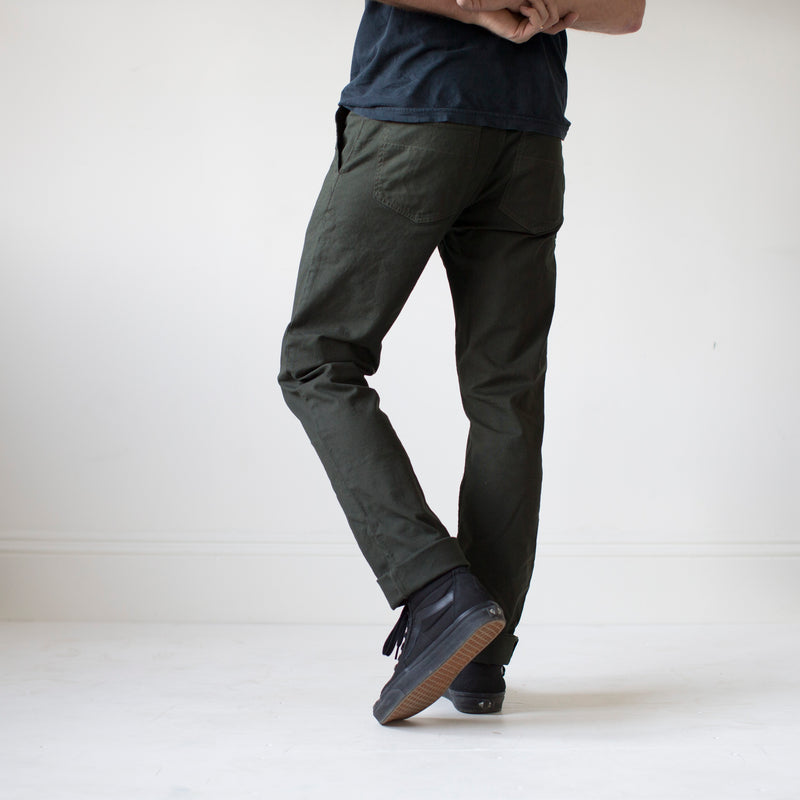 angle: military green  A model wears Raleigh Denim Workshop Jones thin fit pants in dark green, back view