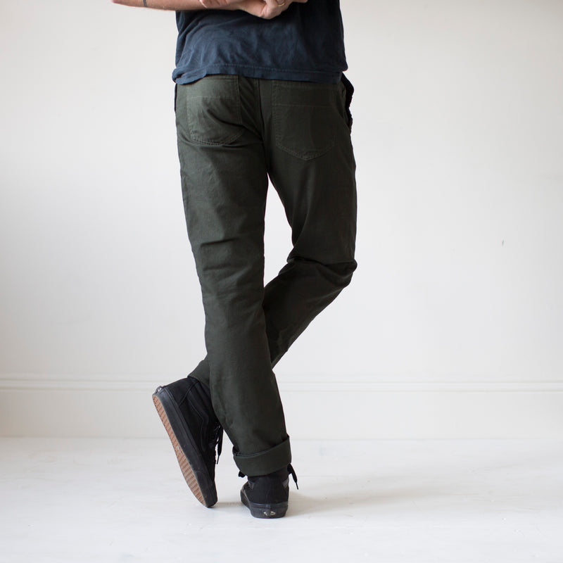 angle hover: military green  A model wears Raleigh Denim Workshop Jones thin fit pants in dark green, back view
