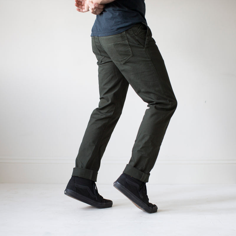 angle: military green  A model wears Raleigh Denim Workshop Jones thin fit pants in dark green, side view