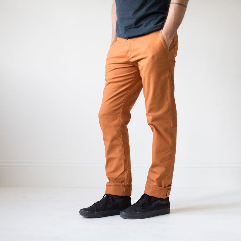 angle: chestnut  A model wears Raleigh Denim Workshop Jones thin fit pants in chestnut orange, front view