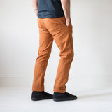 angle: chestnut  A model wears Raleigh Denim Workshop Jones thin fit pants in chestnut orange, back view