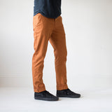 angle: chestnut  A model wears Raleigh Denim Workshop Jones thin fit pants in chestnut orange, side view