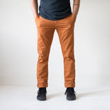 angle hover: chestnut  A model wears Raleigh Denim Workshop Jones thin fit pants in chestnut orange, front view