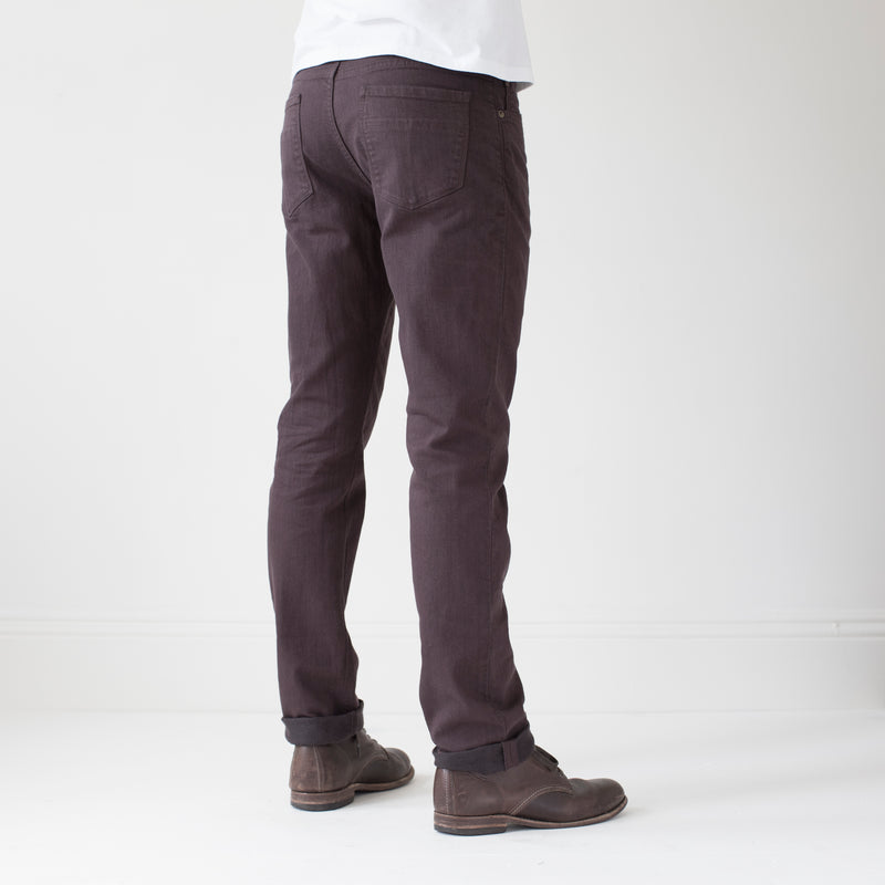 angle: walnut  A model wears Raleigh Denim Workshop Alexander work fit stretch pants in brown walnut, back