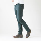 angle: juniper  A model wears Raleigh Denim Workshop Alexander work fit stretch pants in green-blue juniper, side view