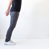 angle: smoke  A model wears Raleigh Denim Workshop Martin thin taper fit stretch pants in gray smoke, side view