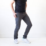 angle hover: smoke  A model wears Raleigh Denim Workshop Martin thin taper fit stretch pants in gray smoke, front view
