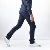 angle: dark fathom  A model wears Raleigh Denim Workshop Martin thin taper fit stretch pants in navy blue dark fathom, side view