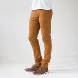 angle hover: chestnut  A model wears Raleigh Denim Workshop Alexander stretch pants in orange chestnut, front view