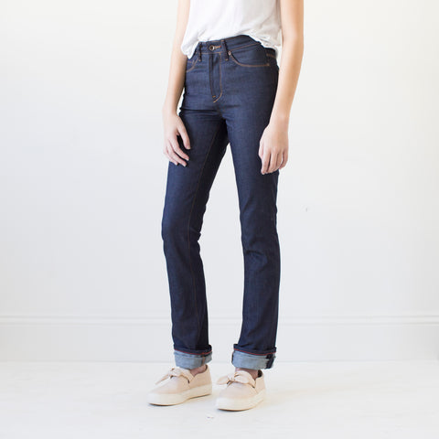 angle: indigo | A model wears Raleigh Denim Workshop Madison high-rise straight leg raw dark jeans, front view