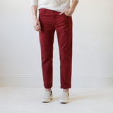 angle: poinsettia  A model wears Raleigh Denim Workshop women's pants in the Gates fit in red poinsettia, front