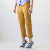 angle: turmeric  A model wears Raleigh Denim Workshop women's pants in the Gates fit in turmeric yellow, front