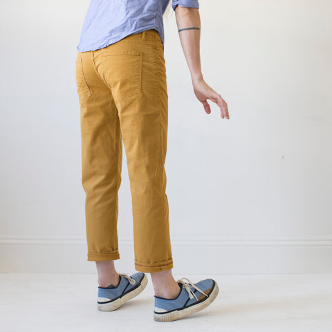 angle: turmeric | A model wears Raleigh Denim Workshop women's pants in the Gates fit in turmeric yellow, front