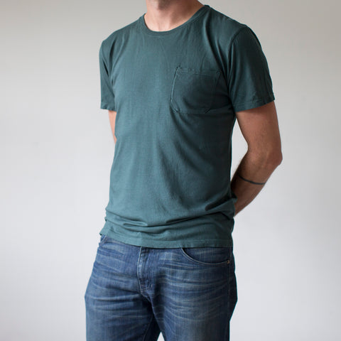 angle: juniper | A model wears Raleigh Denim Workshop cotton/modal pocket crew neck tee in green juniper