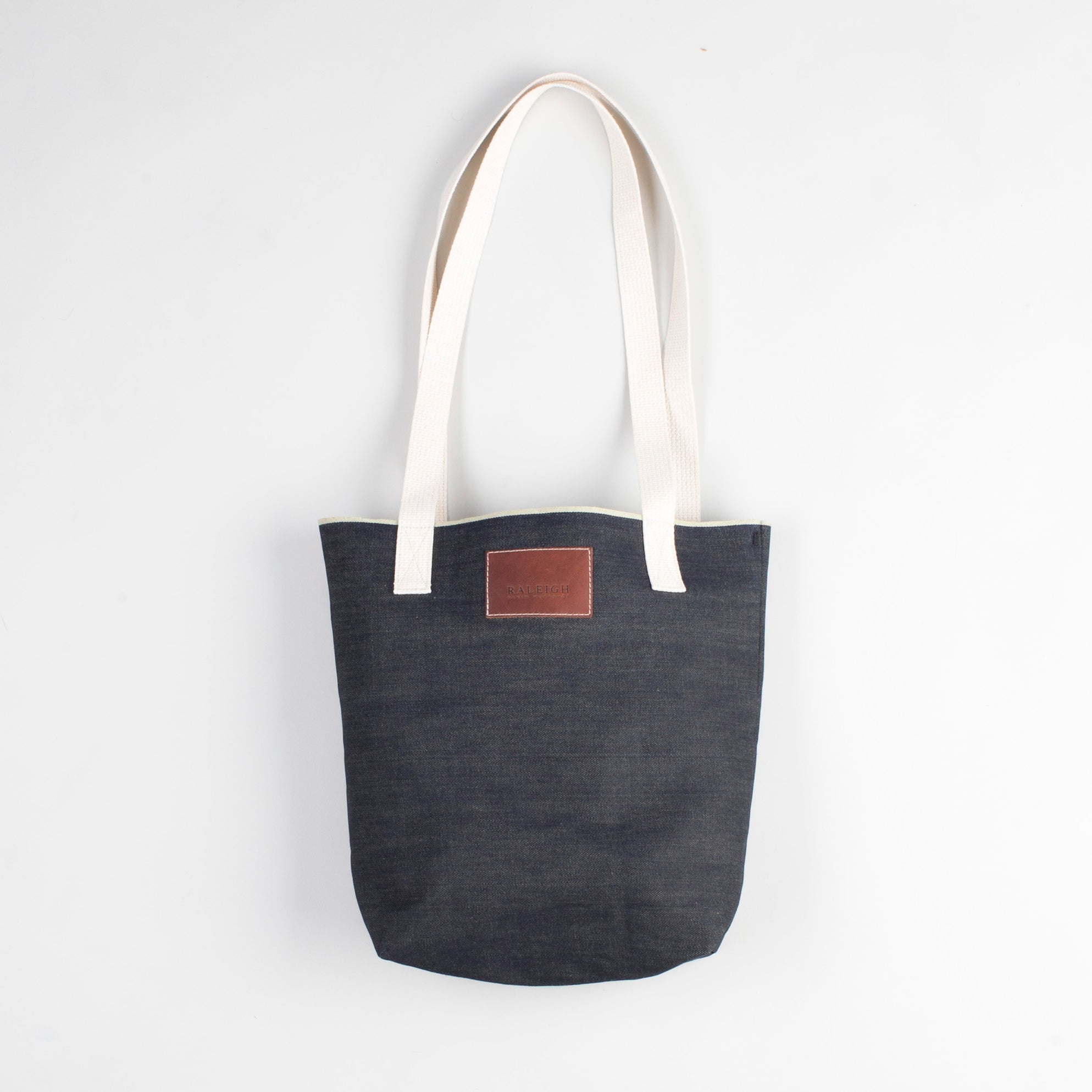 angle: denim  Raleigh Denim Workshop denim tote bag with cream handles and leather patch
