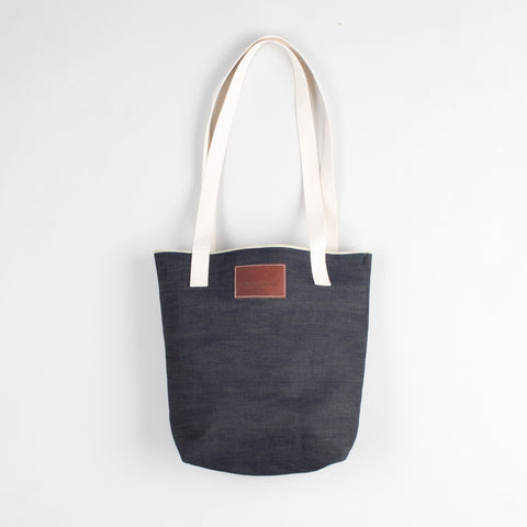 angle: denim | Raleigh Denim Workshop denim tote bag with cream handles and leather patch