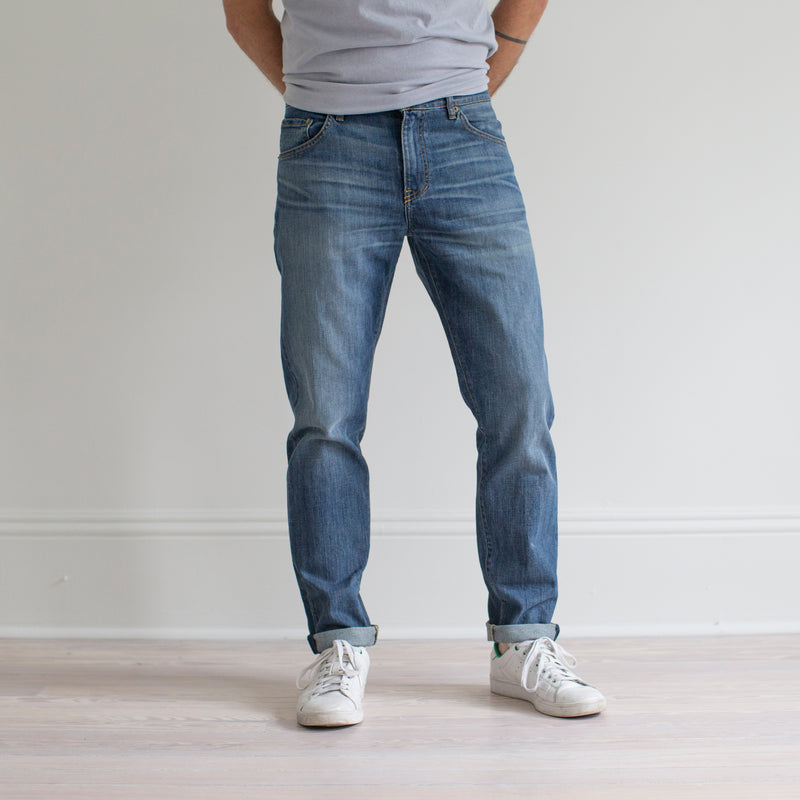 angle: pilot  A model wears Raleigh Denim Workshop Graham fit pants in blue, front view