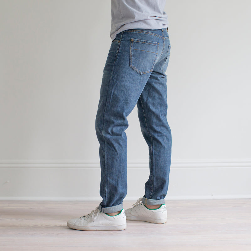 angle: pilot  A model wears Raleigh Denim Workshop Graham fit pants in blue, side view