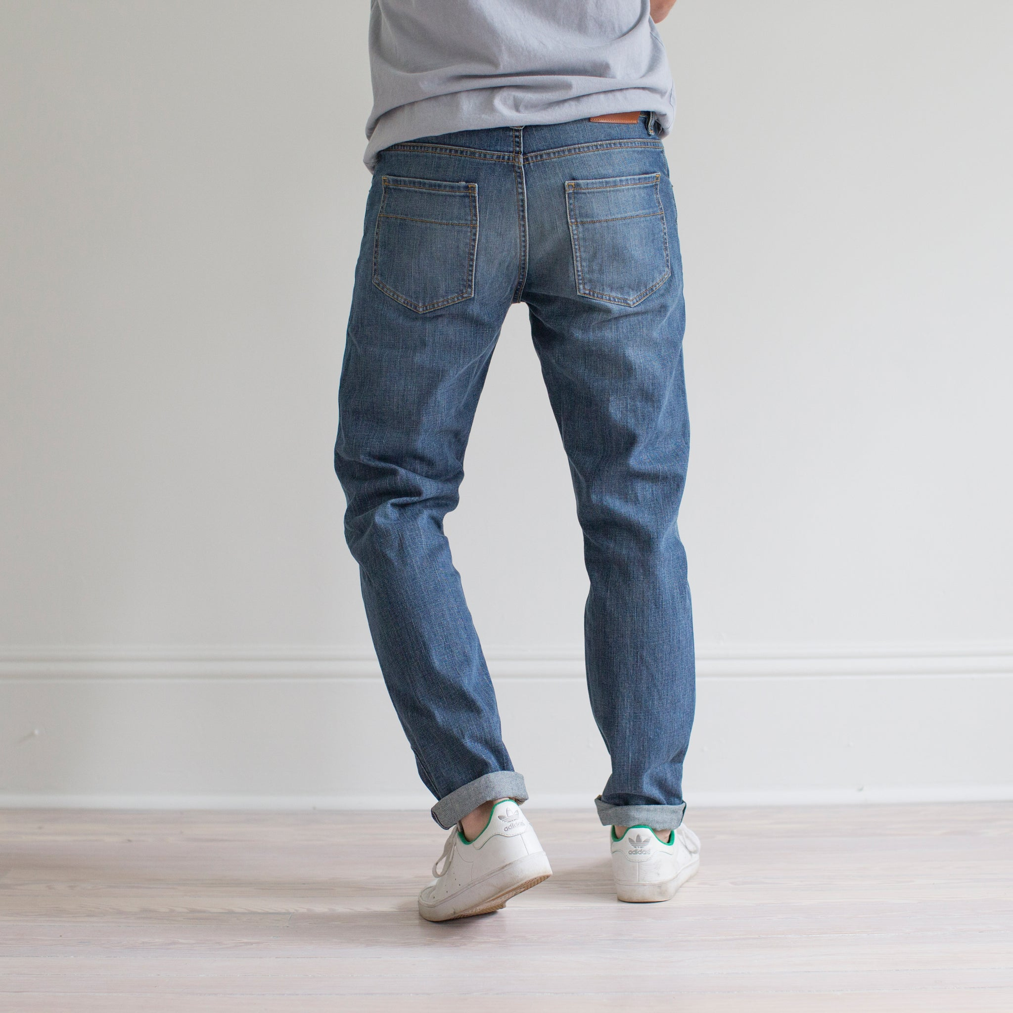 angle: pilot  A model wears Raleigh Denim Workshop Graham fit pants in blue, back view