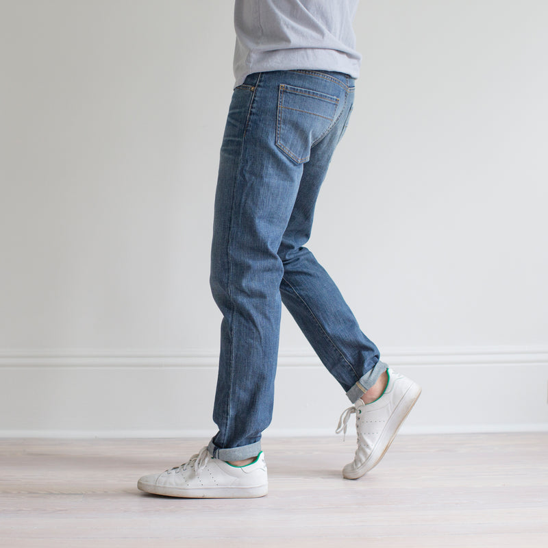 angle hover: pilot  A model wears Raleigh Denim Workshop Graham fit pants in blue, side view