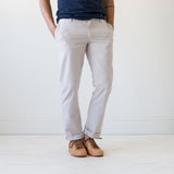 angle: cloud grey  A model wears Raleigh Denim Workshop men's Jones thin fit canvas pants in light gray cloud grey.