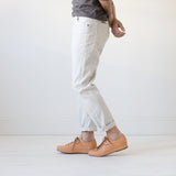 angle: natural heather  A model wears Raleigh Denim Workshop Graham work taper fit jeans in white, side view