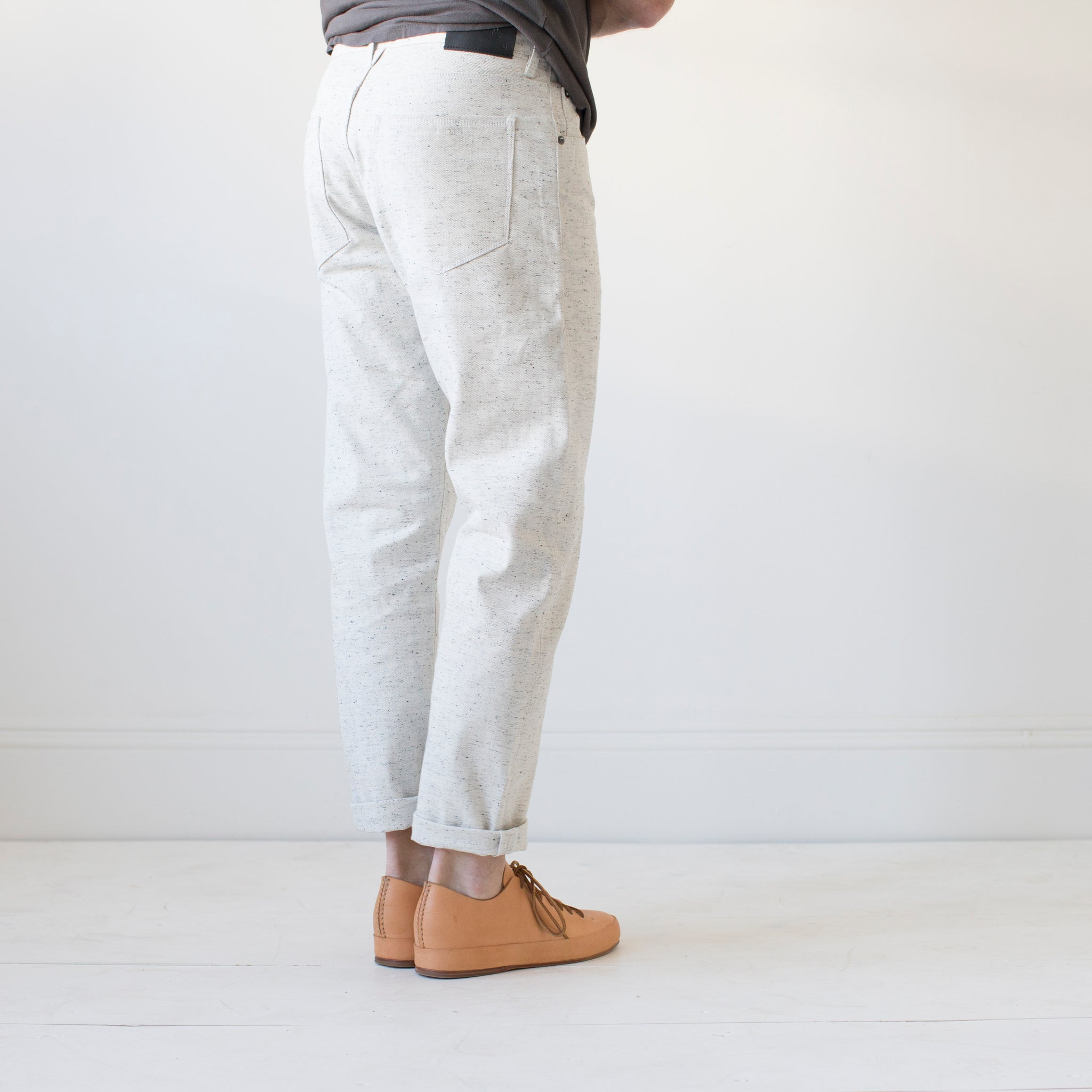 angle: natural heather  A model wears Raleigh Denim Workshop Graham work taper fit jeans in white, back view