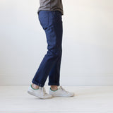 angle: chevron II  A model wears Raleigh Denim Workshop Jones thin fit selvage raw jeans in blue, side view