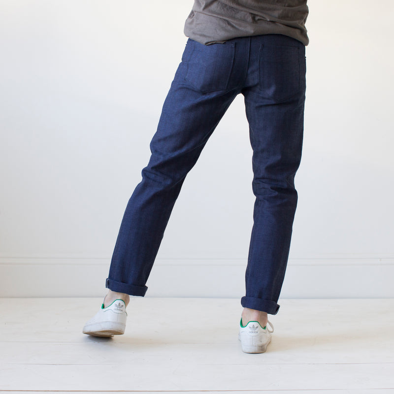 angle: chevron II  A model wears Raleigh Denim Workshop Jones thin fit selvage raw jeans in blue, back view