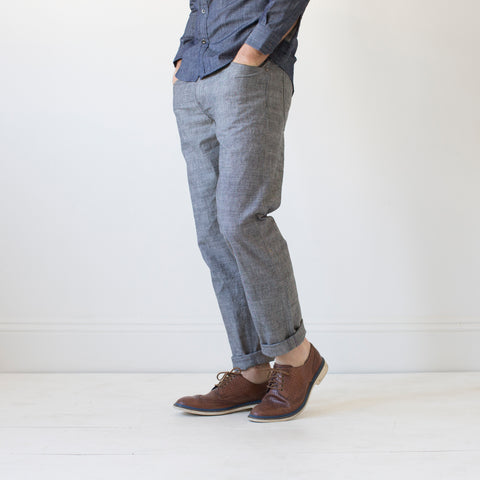 angle: grayhall | A model wears Raleigh Denim Workshop Graham work taper fit jeans that are in gray, front view