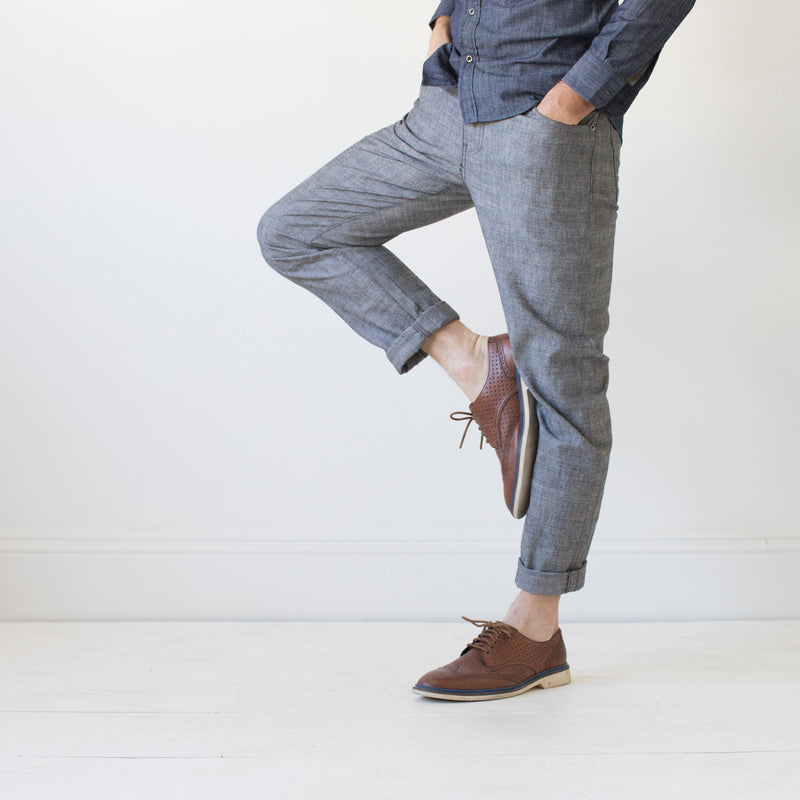 angle: grayhall  A model wears Raleigh Denim Workshop Graham work taper fit jeans that are in gray, front view