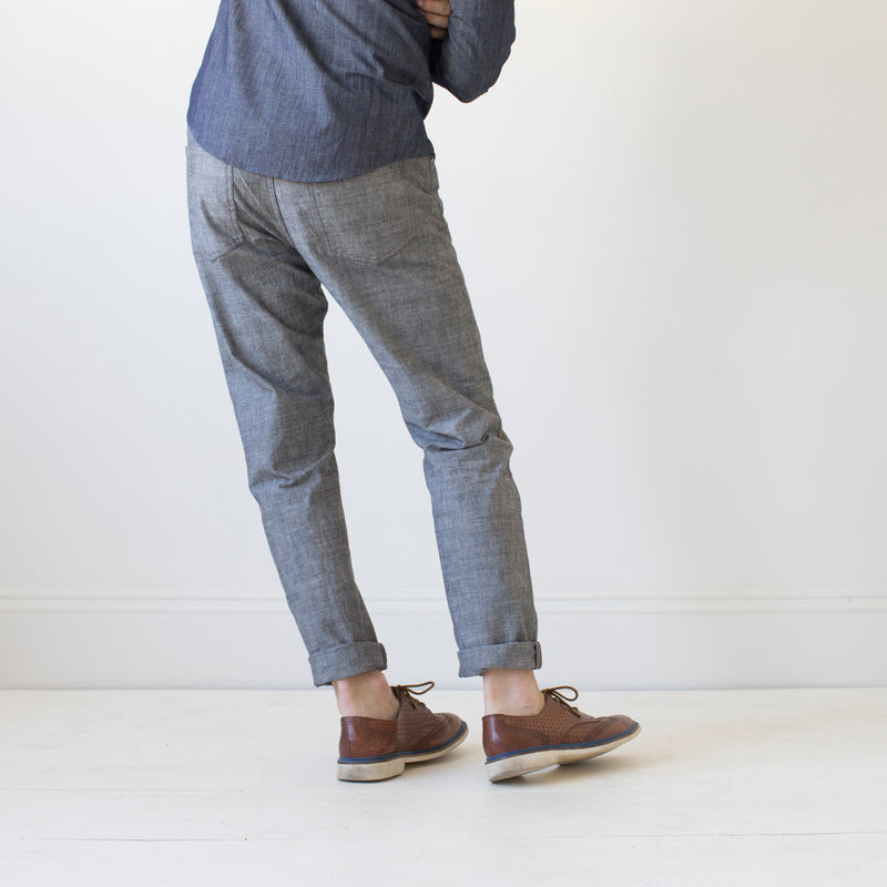 angle: greyhall  A model wears Raleigh Denim Workshop Graham work taper fit jeans that are in gray, back view