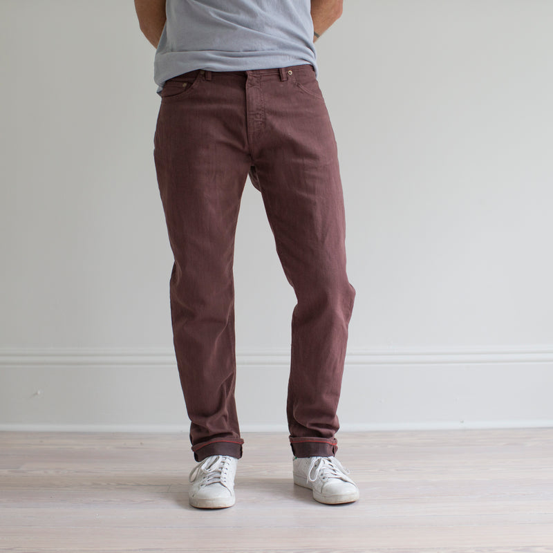 angle: russet  A model wears Raleigh Denim Workshop Alexander fit stretch pants in maroon, front view