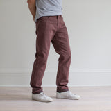 angle hover: russet  A model wears Raleigh Denim Workshop Alexander fit stretch pants in maroon, side view