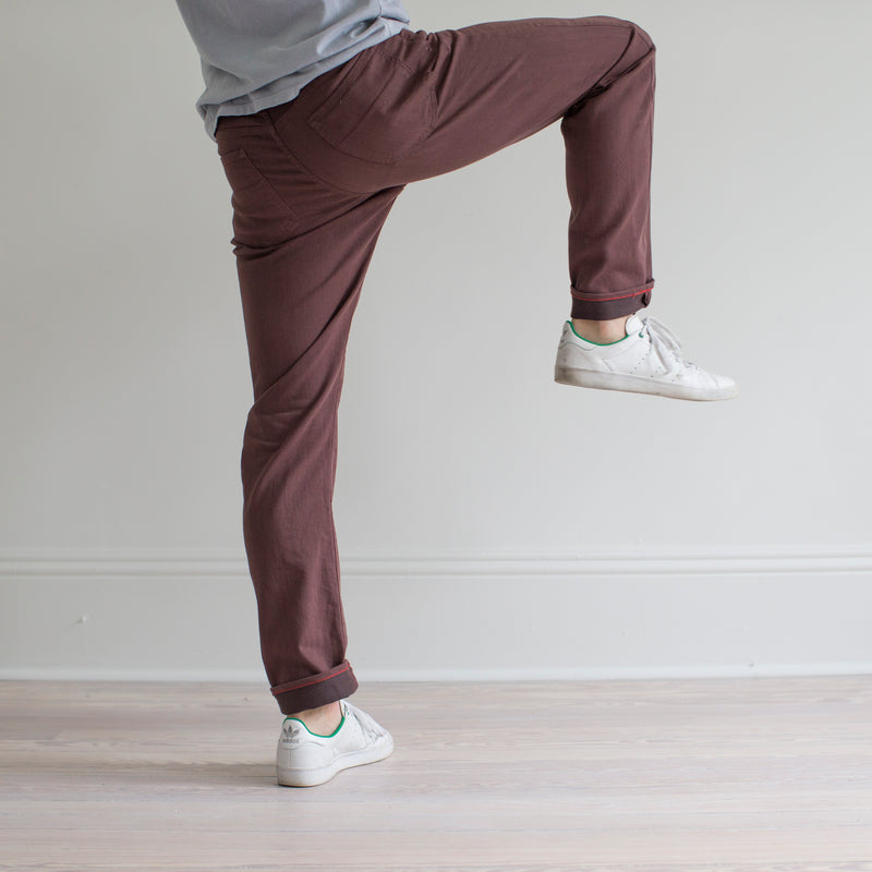 angle: russet  A model wears Raleigh Denim Workshop Alexander fit stretch pants in maroon, side view