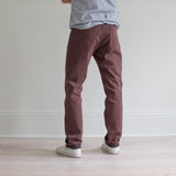 angle: russet  A model wears Raleigh Denim Workshop Alexander fit stretch pants in maroon, back view