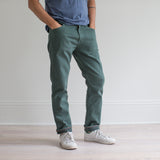 angle hover: hemlock  A model wears Raleigh Denim Workshop Alexander fit stretch pants in green, side view