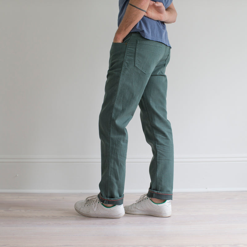 angle: hemlock  A model wears Raleigh Denim Workshop Alexander fit stretch pants in green, side view