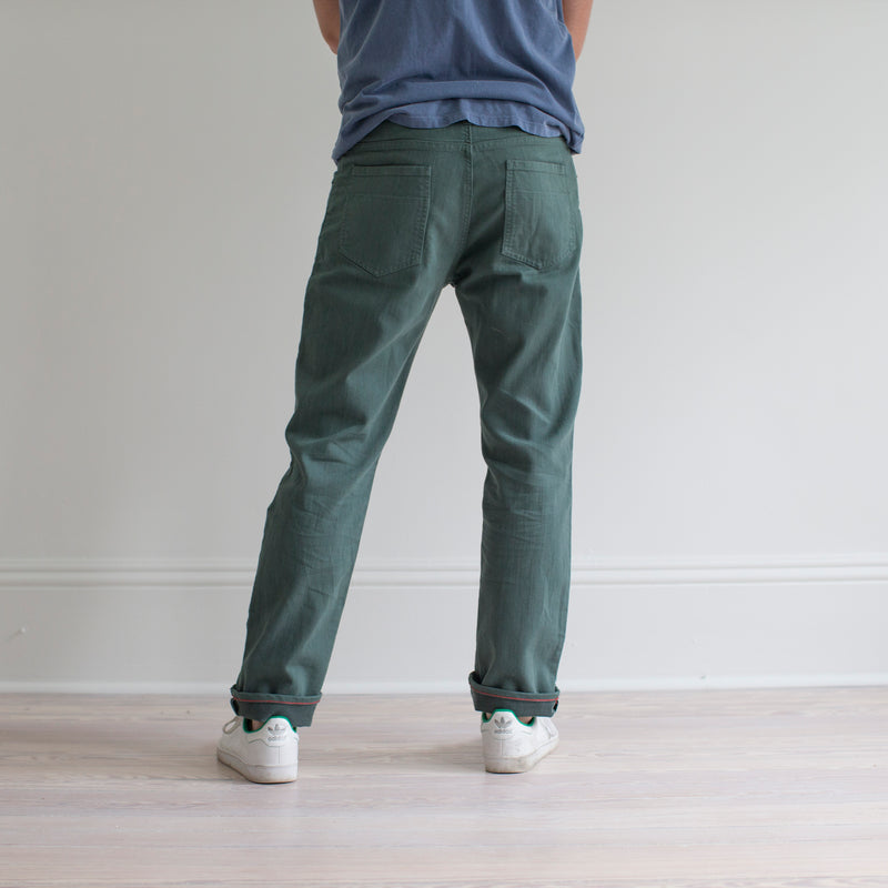 angle: hemlock  A model wears Raleigh Denim Workshop Alexander fit stretch pants in green, back view