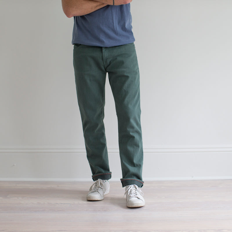 angle: hemlock  A model wears Raleigh Denim Workshop Alexander fit stretch pants in green, front view