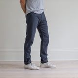 angle hover: iron blue  A model wears Raleigh Denim Workshop Alexander fit stretch pants in blue, side view
