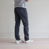 angle: iron blue  A model wears Raleigh Denim Workshop Alexander fit stretch pants in blue, back view