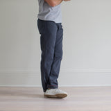 angle: iron blue  A model wears Raleigh Denim Workshop Alexander fit stretch pants in blue, side view