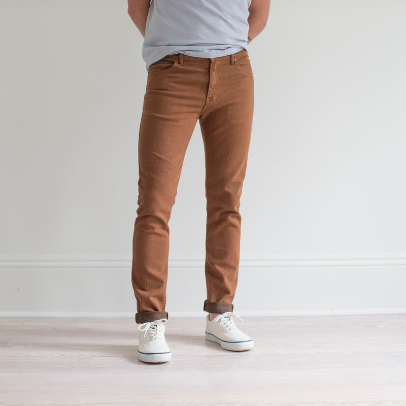 angle hover: whiskey  A model wears Raleigh Denim Workshop Martin fit stretch pants in brown, side view